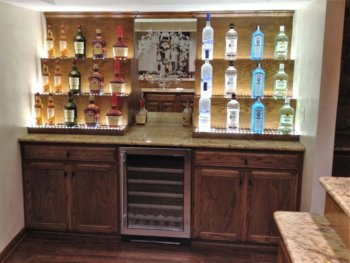 Oak bar with multi tier lighted liquor storage, wine fridge and mirror in red oak.