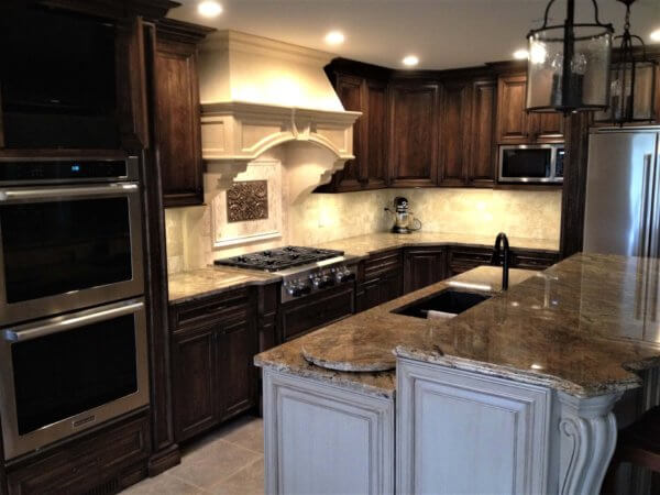 Dark stained maple kitchen with custom range hood, glazed and enameled island, and granite countertops.