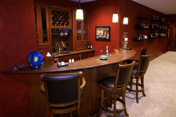 Custom Bar Seating Wine Rack in Wichita KS with beaded curved bar back and custom cabinetry in cherry wood.