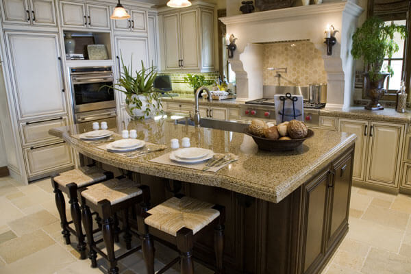 Granite Kitchen Island Bar Seating with large custom range hood and high end appliances.