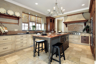 Luxury kitchen cabinets with stained and painted pieces. Faux finished range hood with wood accents and corbels.