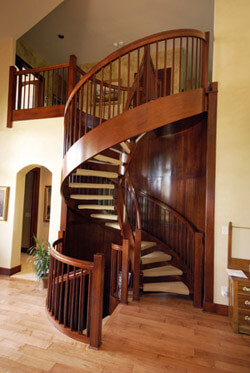 Custom built spiral stair case in cherry with solid cherry treads and carpeted runners in Wichita, Ks.
