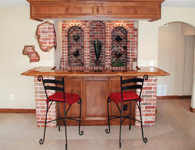 Knotty alder custom built basement bar with brick accents and wood bar top with saloon edge. Brick and wood wine racks with alder soffit.