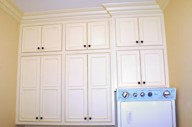 Custom built laundry room cabinetry with beaded face frames and flush mitered doors in off white enamel.