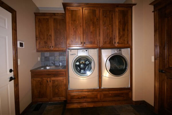 Job built knotty Alder laundry cabinetry with built in washer and dryer and mudroom sink with slate tile backsplash.
