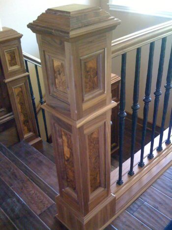 Walnut newel post with burl insets and hand hammered iron balusters with hand scraped oak stair treads