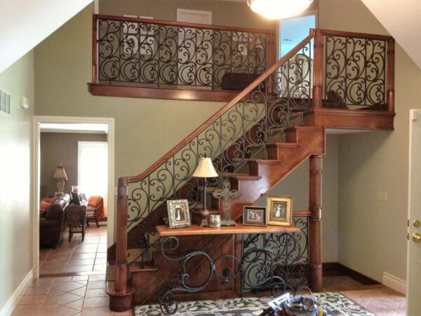 Cherry staircase with over the post rails, welded railing panels and our custom turned newel posts.