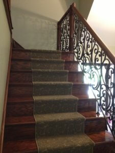 Welded Iron handrail panel with custom cherry posts, over the post rails and solid oak treads and risers