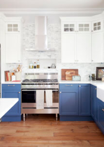 White uppers blue lowers on cabinetry with quartz top.