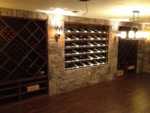 Custom built wine room in oak with racks, horizontal displays and bulk storage with stone veneer and handscraped floor
