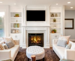 Floor to ceiling white fireplace with bookcases and TV above.