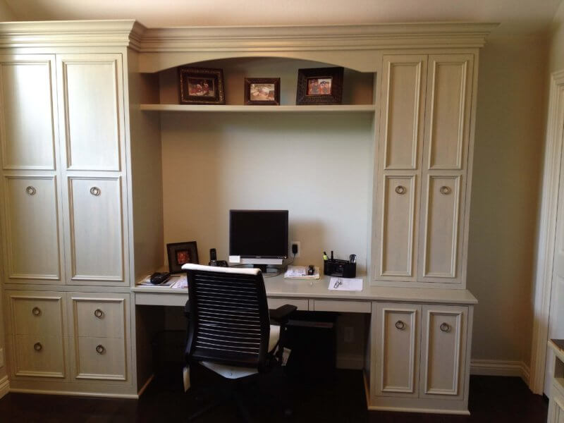 Custom built-in desk cabinetry with hidden printer storage in cool green/grey stain.