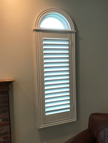 Enameled plantation shutter with custom wood frame and round top trim above