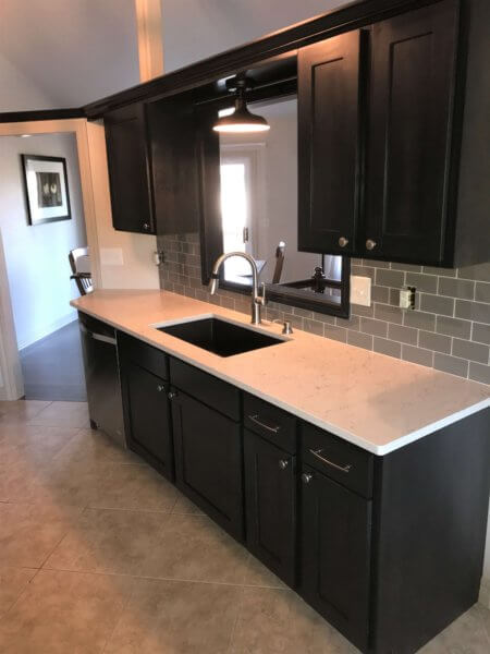 Dark stained maple refaced cabinets with shaker style doors and ceasarstone countertop with glass backsplash tiles.