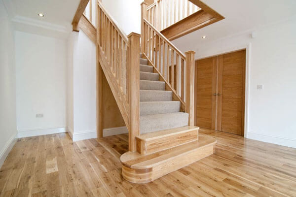 Beautiful staircase in light wood with carpeted treads and wood newel posts.