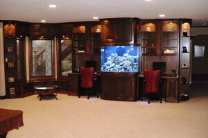 Custom built-in desks in maple with bow front fishtank, seating area and curved curio cabinets in Wichita, ks.