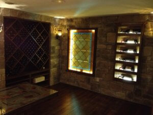 Custom wine cellar with magnum storage, racks, stone veneer on the walls and scraped floring with antique stained glass window.