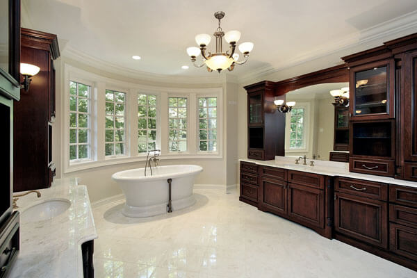 Chandelier and bay window in custom built bathroom with maple cabientry and quartz counter tops.