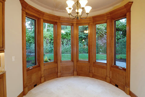 Custom trimmed windows with crown molding accents in maple wood.