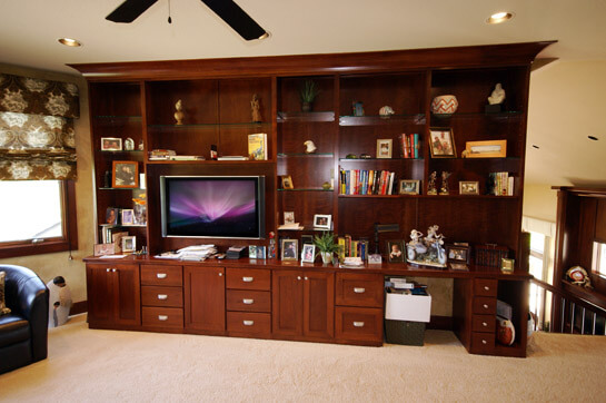 Cherry wood built in entertainment center with glass shelving.
