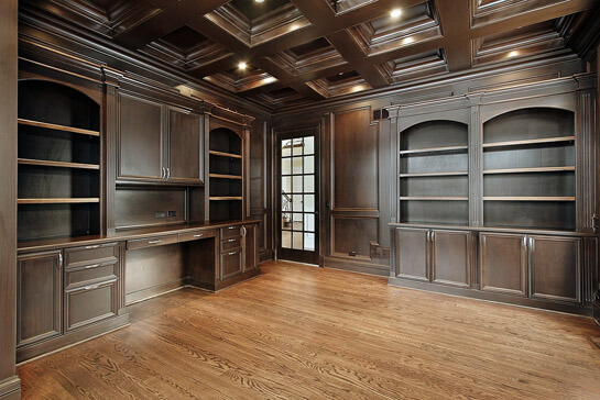 Elegant custom built in office with coffered ceiling, large custom desk and bookcases with fluted columns.