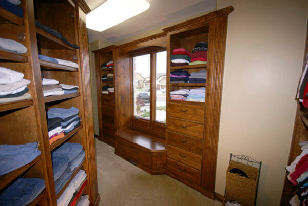 Knotty alder custom closet wood work with cedar lined bench, dressers and adjustable sweater racks