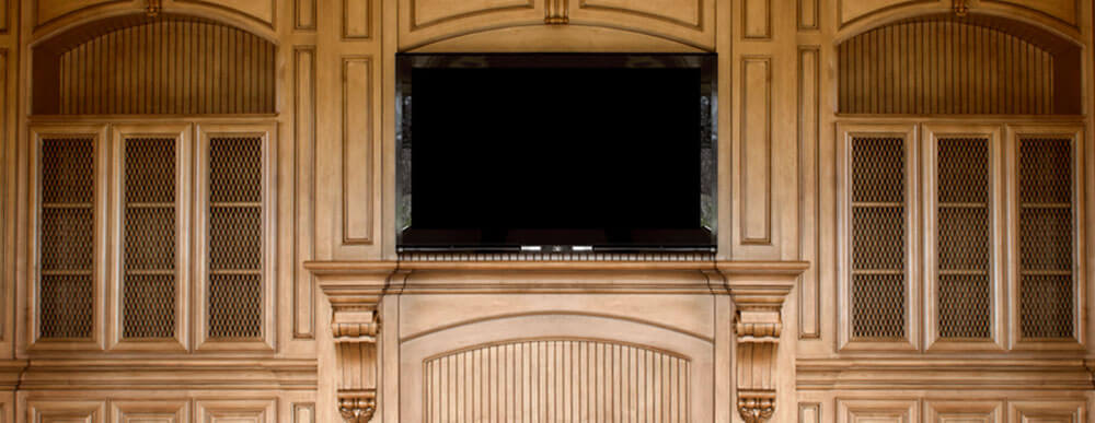 Custom built entertainment center with glass doors, arched top cabinets and carved cobels.
