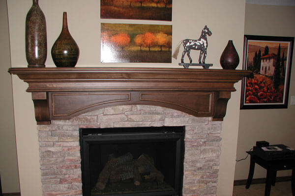 Custom fireplace mantel Wichita with arched panels and hand made corbels.