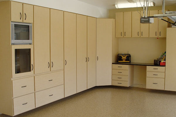 Custom built garage storage cabinets with workbench and space for a tv.