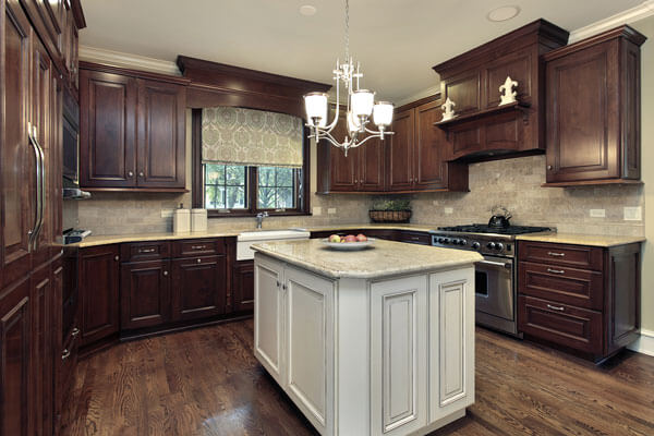 Rich dark stained kitchen cabinets accentuated by a painted island, nice lighting and high end appliances.
