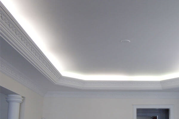 Elaborate crown molding at ceiling soffit with back lighting.