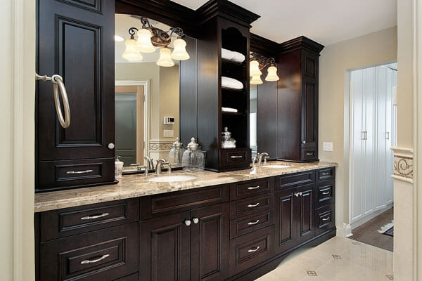 Elegant double vanities with closed and open upper storage in walnut with beatiful bathroom hardware.