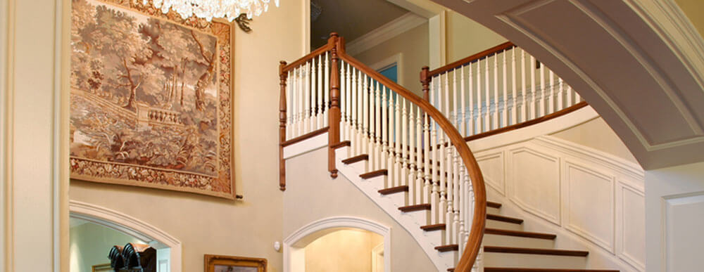 Elegant home stairway with solid wood treads, painted risers, wainscote and skirtboards. Fancy wooden curved railing with stianed custom newels and handrail plus painted balusters.