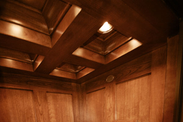 Elevator wood work with ceiling coffer in cherry wood.