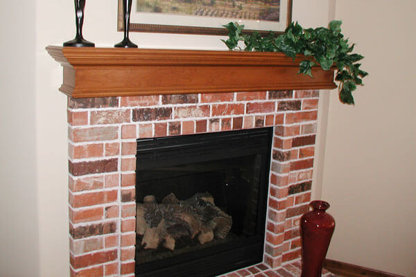 Fireplace mantel wichita in red oak with brick hearth.