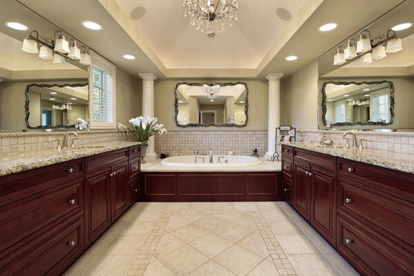His and her vanities with tub in cherry with raised panel cabinet doors and lots of mirrors and columns