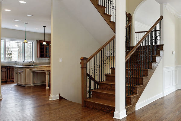 Iron balusters with wood handrails and newel posts on custom built staircase.