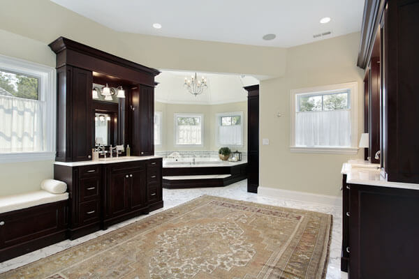 Large high end bathroom with dark stained walnut cabinetry, walnut tub deck and walnut seating area.