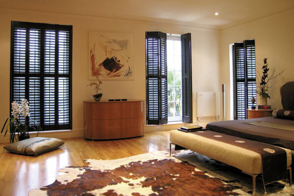 Large plantation shutters finished in black paint.