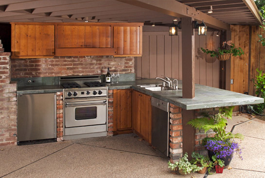Covered outdoor kitchen with wood cabinets and stainless appliances.