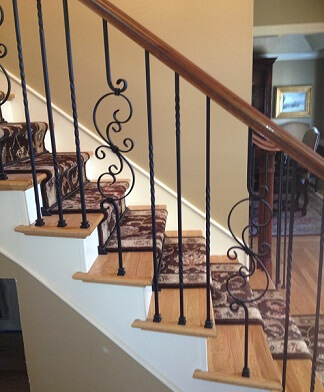 Iron balusters with cherry handrail and oak treads.