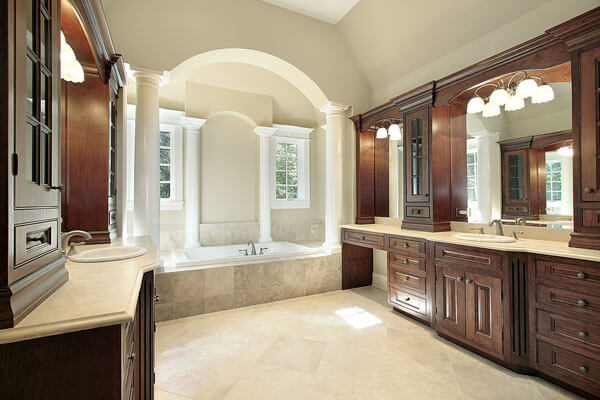 Stylish bathrooms with columns, beautiful custom bath cabinetry with travertine floors and countertops.