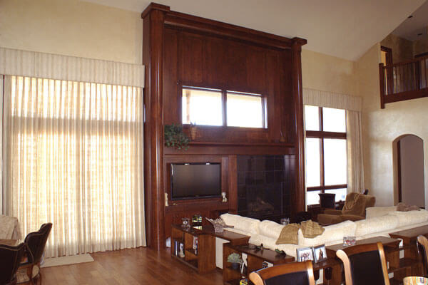Huge wood columns flanking entertainment center and fireplace.