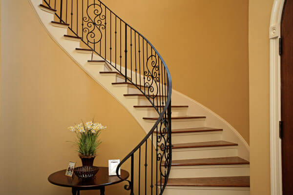 Curved staircase with iron railing, painted risers and skirtboards with solid oak treads.