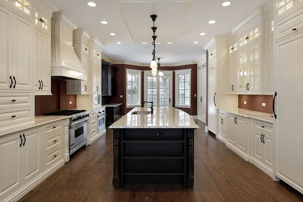 Off white kitchen cabinets with dark island, wood floors and stone counter tops. Ample lighting and custom range hood with high end stainless appliances.