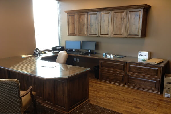 Custom knotty alder commercial cabinetry and desk in local bank