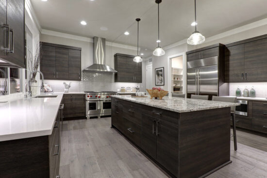Modern grey cabinetry with quartz countertops, high end appliances and a stainless range hood.