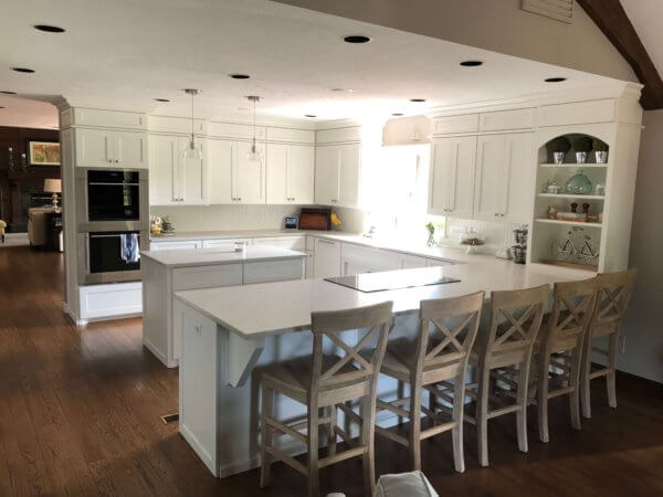 Refaced cabinets in maple with Alabaster white enamel, quartz countertops and Wolf appliances with quartz counters.