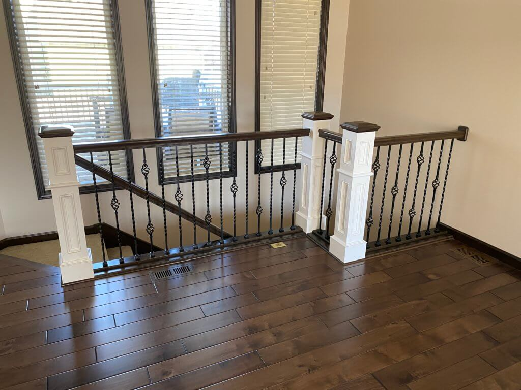Painted newel posts with stained caps and iron balusters by Records Custom Cabinets and Trim Carpentry